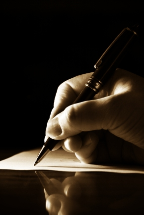 Hand writing a note on a sheet of paper with a pen